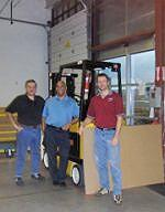 Three people from H&B Disher Courier in front of a forklift truck
