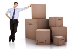 Man leaning against boxes mentioning fragile
